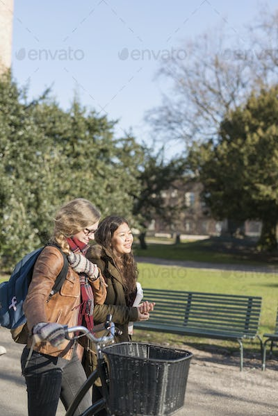 Teenage friends with bicycle walking on footpath in college campus