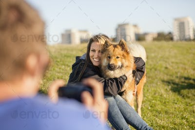 Cropped image of man photographing happy girlfriend embracing dog at park