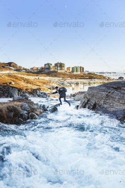 Hiker jumping over river