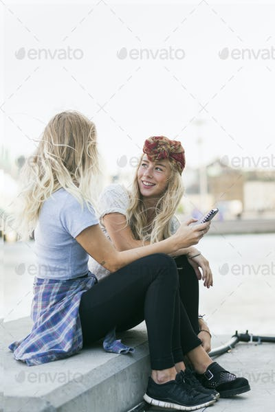 Female college students with mobile phone while sitting on retaining wall by river