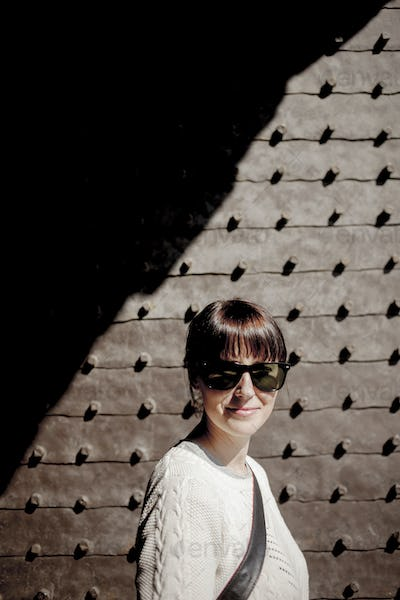 Portrait of mid adult woman wearing sunglasses against wall