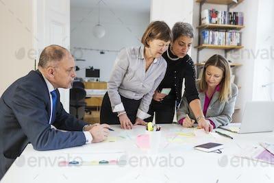 Businesswomen communicating over reminder notes at office desk