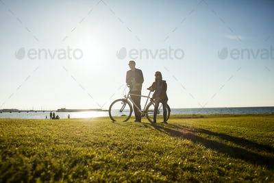 Couple with bicycle on grassy landscape by sea against sky