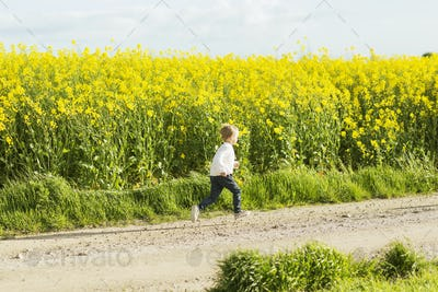 Boy running on dirt road at rapeseed field