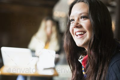 Happy young woman looking away in cafe