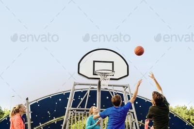 Low angle view of friends playing basketball at park against clear sky