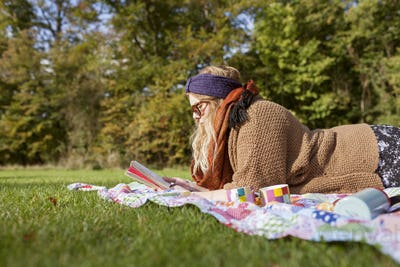 Side view of young woman reading novel while lying on picnic blanket at forest
