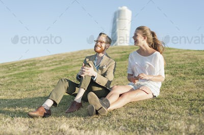 Happy couple sitting on grassy hill in city