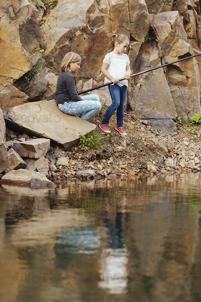 Sisters on rocks fishing in lake