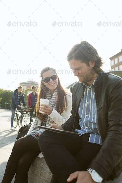 Businesswoman having coffee while businessman using digital tablet in city against clear sky