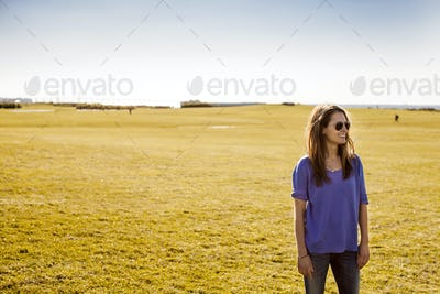 Happy woman standing at park against clear sky