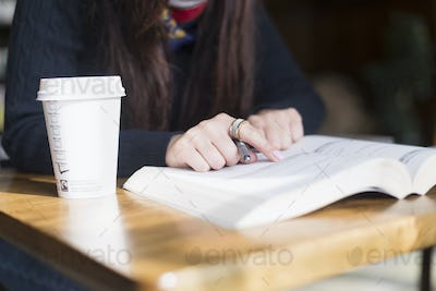 Midsection of woman pointing on text in book at station cafe