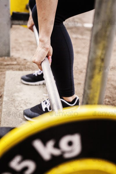 Low section of woman lifting barbell at park