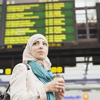 Low angle view of woman holding coffee cup while standing at railroad station