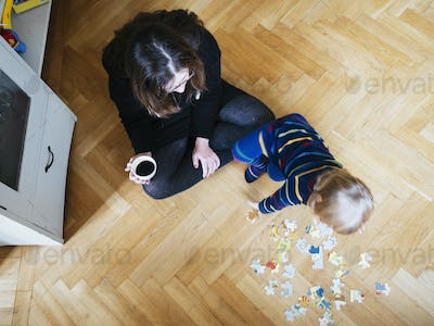 High angle view of woman holding coffee cup while looking at baby girl with puzzle pieces