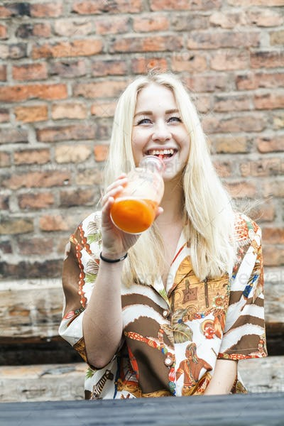 Happy young woman drinking juice while sitting at cafe backyard