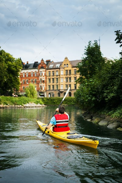 Rear view of man kayaking on river in city
