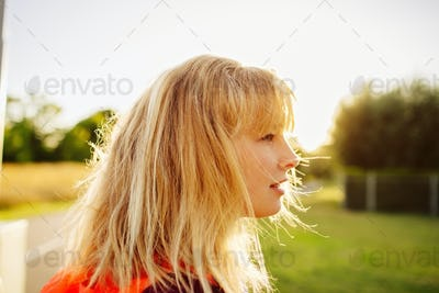 Side view of female athlete looking away at park during sunset