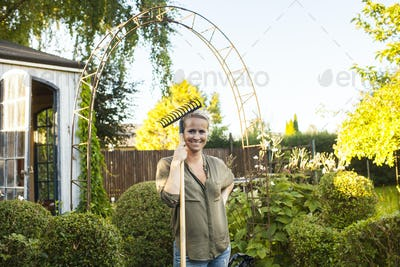 Portrait of happy woman with gardening fork in garden