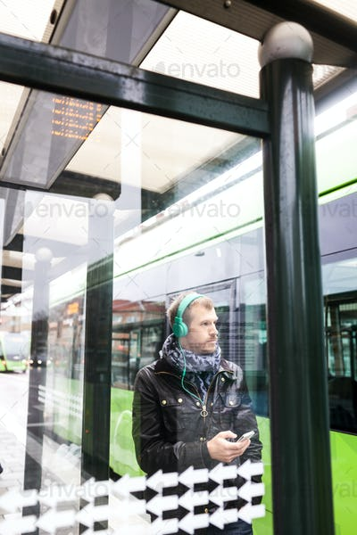 Man listening music while waiting at bus stop