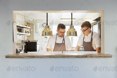Young chefs working together at serving window in restaurant
