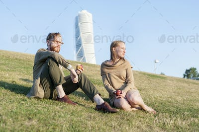 Low angle view of couple eating apples on grassy hill against Turing Torso