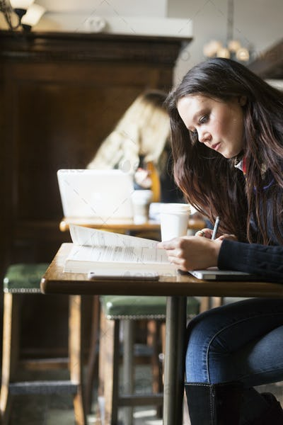 Young woman studying at table in station cafe