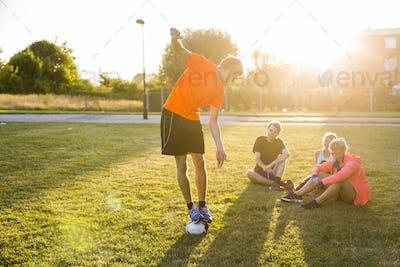 Sporty friends looking at man balancing on soccer ball at park