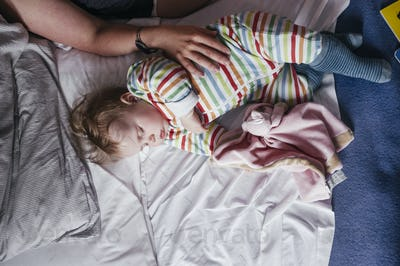 Cropped image of woman touching baby girl on bed