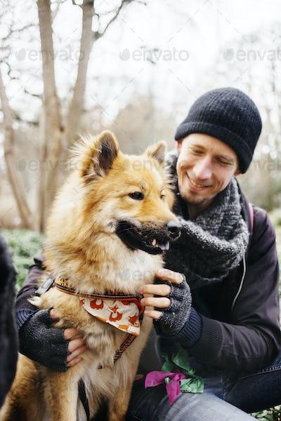 Smiling man looking at Eurasier in park