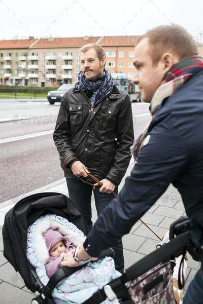 Men with baby on sidewalk by city street