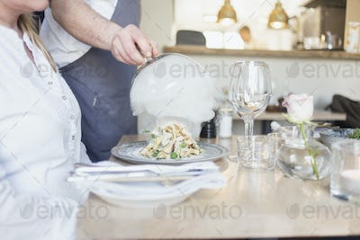 Midsection of waiter lifting cloche from dish for customer in restaurant