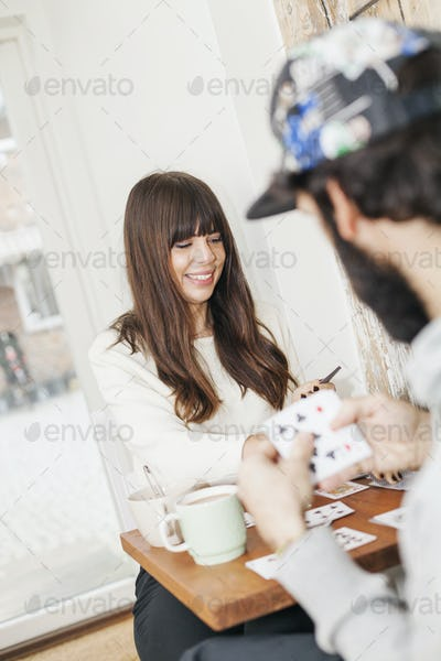 Happy woman playing cards with man in coffee shop