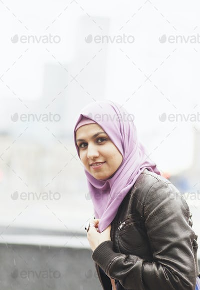 Side view portrait of smiling woman outside railroad station