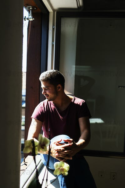 Thoughtful young man sitting on window sill