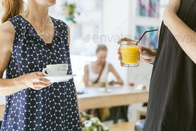 Midsection of man and woman with coffee and juice in coffee shop