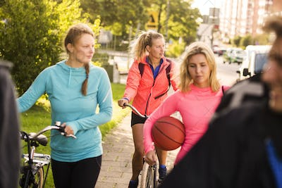 Basketball players walking with bicycles on sidewalk at park