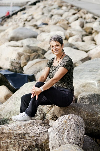 Full length portrait of happy mature woman sitting on rocks at seashore