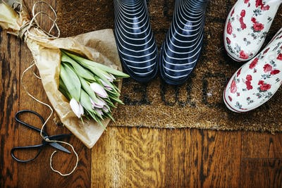 High angle view of gardening boots by tulip bouquet and scissors on hardwood floor