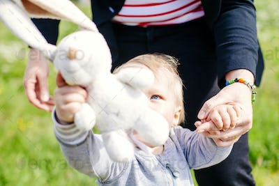 Boy holding stuffed toy while standing by mother on field