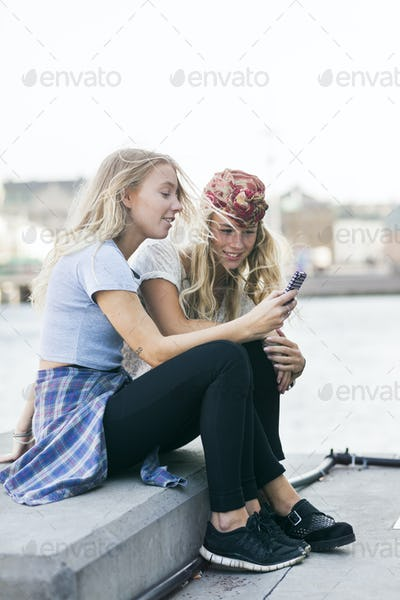 Female college students using mobile phone while sitting on retaining wall by river