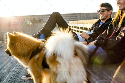 Happy couple with dog relaxing on steps outdoors