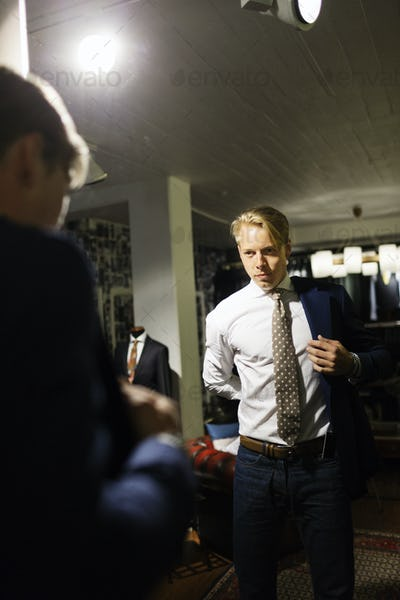 Male customer trying on suit in fitting room at clothing store