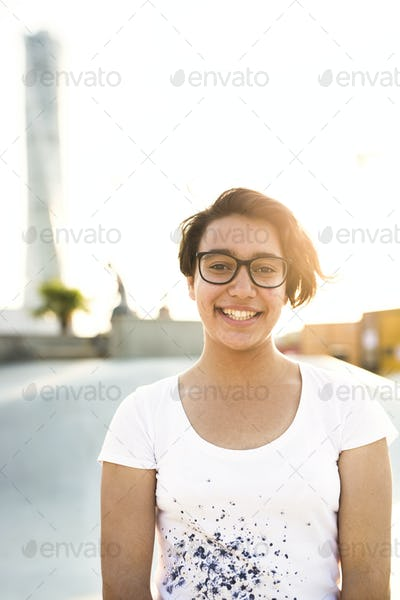 Portrait of smiling teenage girl wearing glasses at skate park