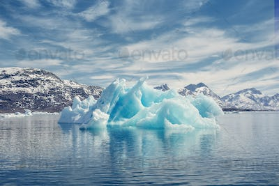 View of icebergs melting in sea by mountains against cloudy sky