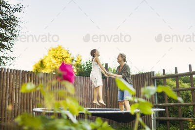 Mother and daughter jumping on trampoline in garden
