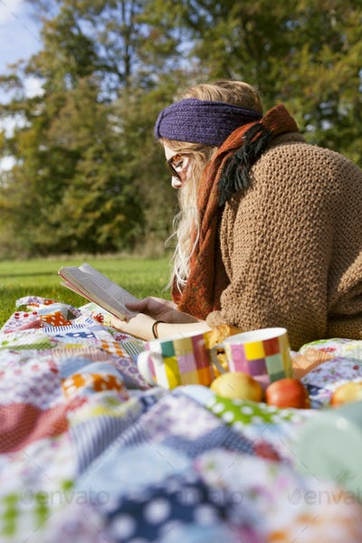 Side view of young woman reading book while lying on picnic blanket at forest