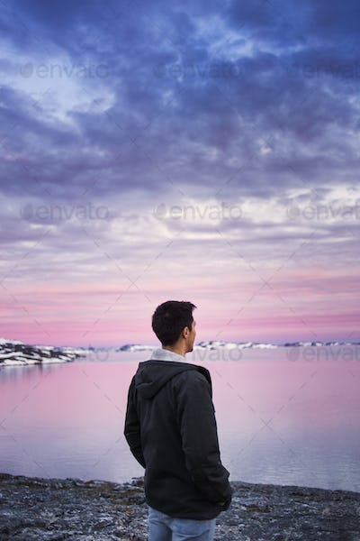 Rear view of young man on shore enjoying the sunset view