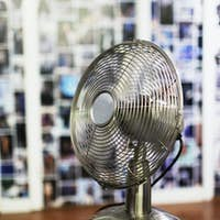 Close-up of electric fan on stool in clothing store