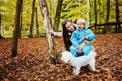Woman looking at crying boy while sitting in forest